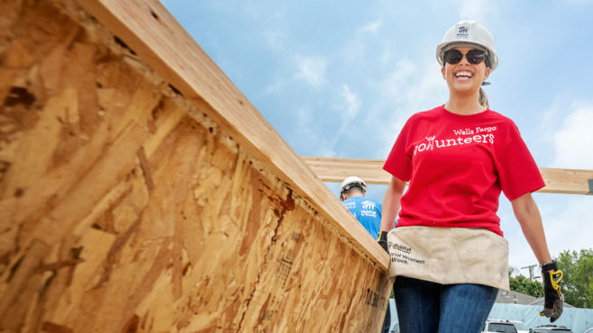 A woman wearing a hard hat, sunglasses, and a red Wells Fargo volunteers T-shirt carries plywood at a construction site.