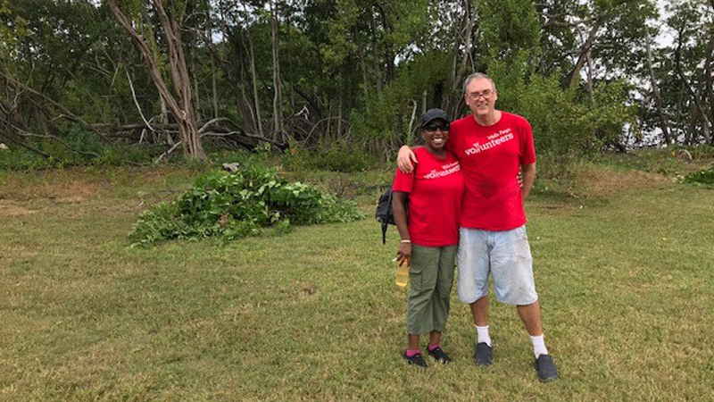 Yvonne Nyakana and Mike Rasco stand beside each other with their arms around each other and smile at the camera. They both wear red shirts that say Wells Fargo volunteers. They are standing on grass in front of a wooded area.