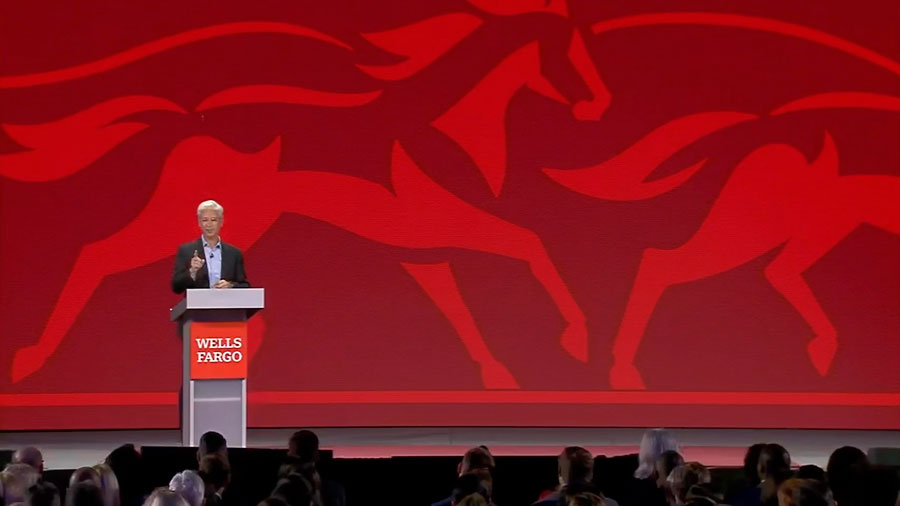 Wells Fargo CEO Charlie Scharf stands behind a lecturn to address an audience of employees. A red silhouette of horses is in the background behind him on stage.