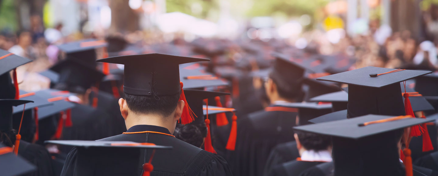 A photo shows the backs of people wearing graduation caps.