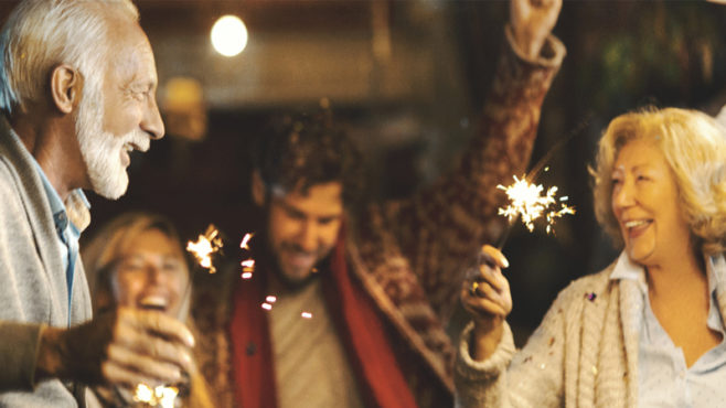 A group of four people smiling. A man and woman are looking at each other and holding lit sparklers.