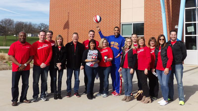 Wells Fargo team members pose with Harlem Globetrotter Zeus McClurkin after providing financial education.