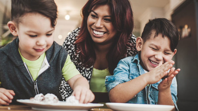 A mother and her two young sons share a laugh as the boys sit at a table and eat cookies.