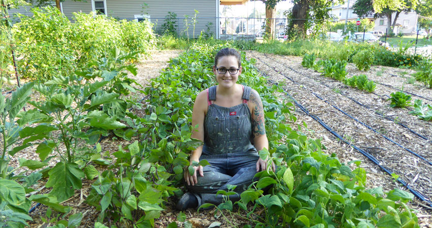 Monika Owczarski, wearing overalls and smiling, sits in the middle of an urban farm with plants in rows. Part of a house stands behind the urban farm area.