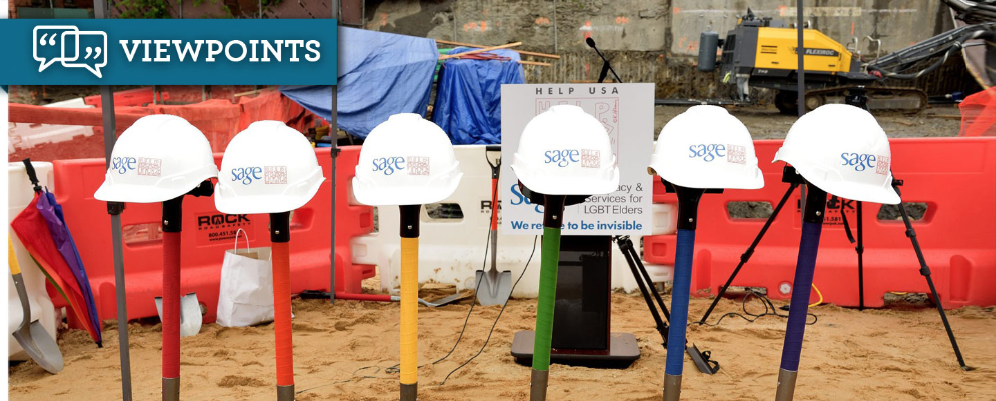 At a groundbreaking ceremony, six shovels stand in the dirt, each topped with a hard helmet with the SAGE logo on it.