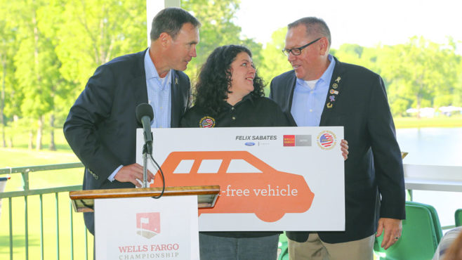 Standing between Jerry Bowen and Ken Eakes at a podium, Tanya Palmer holds a poster representing the payment-free vehicle she was awarded at a ceremony at the Wells Fargo Championship.