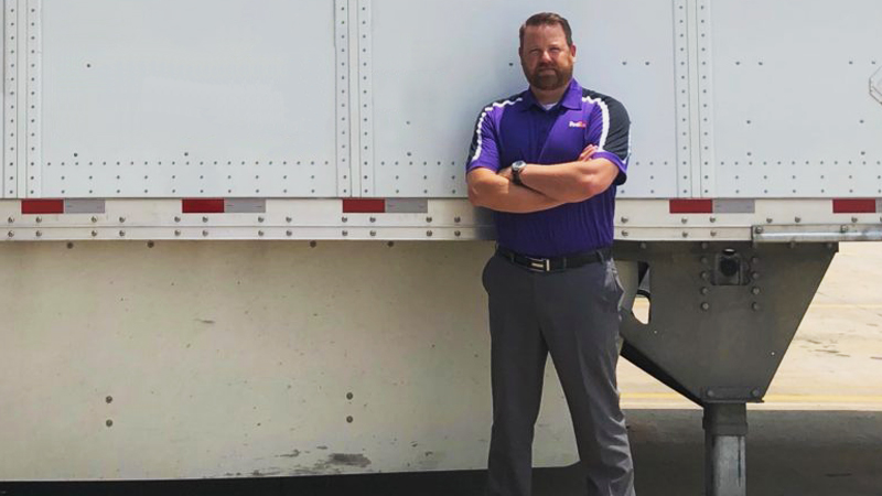 Scott Johnson stands in front of a large trailer.