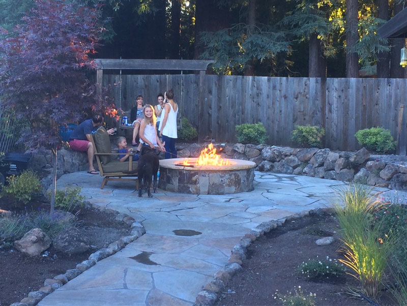 A fire pit with a fire ablaze stands in the middle of an outdoor patio area. Several people are standing and sitting nearby. There is a fence behind the area.