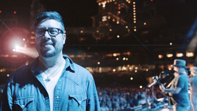 Story Type Indicator - video. Mark Durazo, at a Zac Brown Band concert in San Diego, looks at the camera and smiles. The nighttime, outdoor concert is in the background: Two men are standing at microphones on stage and a crowd of people is below the stage.