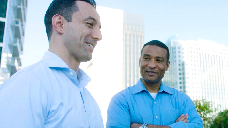 Victor Perez stands to the left of Frank Van Buren as they both smile and wear blue, buttoned-up shirts. Perez is looking straight ahead, but his side profile is seen. Van Buren looks at Perez. Behind them are several skyscrapers.