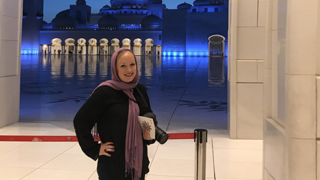 Story Type Indicator - audio. Lynette Hoke poses in front of a mosque in Southwest Asia with a purple scarf wrapped around her head and neck.