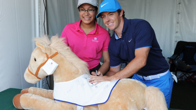 Meghna Mazumdar and Rory McIlroy sign the Wells Fargo plush pony before their start time.